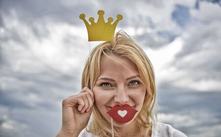 Playful princess. Woman blonde hair hold cardboard tiara or crown and red lips symbol of love sky background. Dream of every girl to become queen. Lady princess posing cheerful with yellow crown