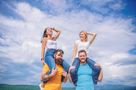 The fun has just begun. Playful couples in love smiling on cloudy sky. Happy men piggybacking their girlfriends. Loving couples having fun activities outdoor. Loving couples enjoy fun together