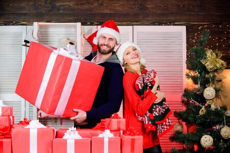 Cute couple. celebrate christmas together. winter season. cheerful man and woman share presents. happy new year. family holiday. couple in love santa hat. gift time. cozy evening with your beloved