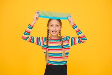 Professional equipment. Comb for tangled hair. Hairdresser supplies. Large comb. Girl long hair hold enormous comb. Hairdresser salon. Combing hair. Cheerful happy smiling little kid with giant comb Stock Photo