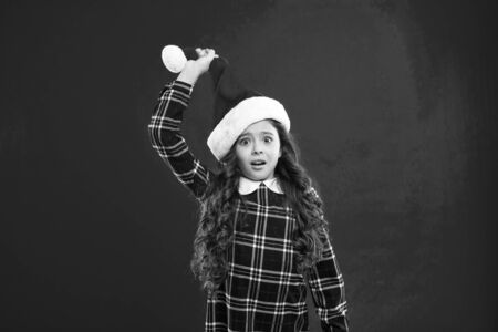 Happy winter holidays. Small surprised girl. Present for Xmas. Childhood. Little girl child in santa red hat. Christmas shopping. New year party. Santa claus kid. Im waiting. Ready for holiday