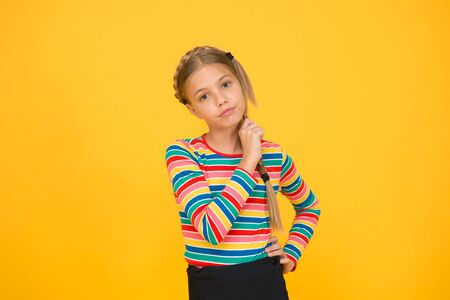 Little girl. Small child with cute braids hairstyle on yellow background. Child care concept. Preteen girl colorful clothes. Childrens shop store mall. Goods for teens. Adorable girl beautiful face