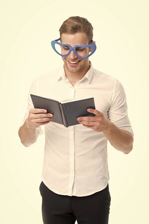 Romantic man learn poetry by heart. Romantic ideas for valentines day. Romantic poetry concept. Man handsome well groomed guy wear heart shaped glasses and hold book. Macho read romantic poetry
