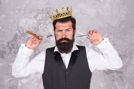Cut and shave. Big barber boss in shaving. Big boss hold shaving razor and scissors. Bearded big boss wear jewelry crown on abstract background. Barber in luxury barbershop. He is big boss here