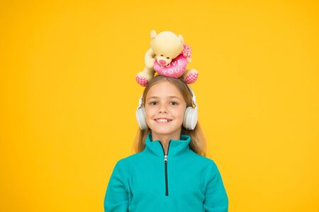 A toy bear hug for you. Happy small child hold soft toy on head. Little girl smile with valentines toy. Teddy bear with love you inscription. Plaything. Valentines day. Toy shop. Buy gifts for kids Stock Photo