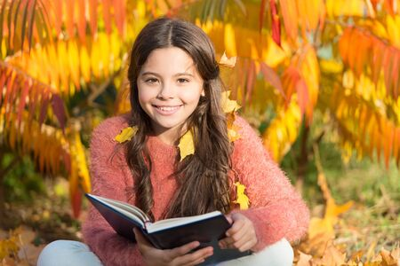 Good book is good companion. Happy small child read book on autumn landscape. Cute little girl enjoy reading book outdoor. Book into the future. Library. Bibliopole