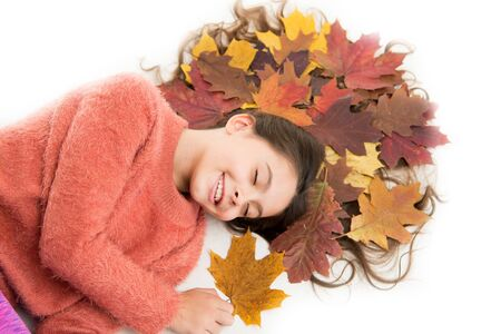 Dry maple leaves in hairstyle. Fall season concept. Hair care in autumn. Prevent dry split hair ends. Child enjoy fall season. Girl cute kid long hair lay on white background with fallen leaves Stockfoto