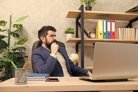 Responding on business e-mail. Brutal businessman in office. Mature man with beard work on laptop. bearded hipster use computer. Male boss working. Keeping business on top with digital technologies