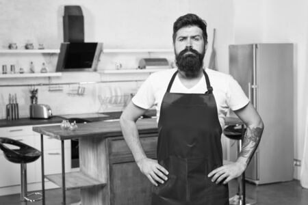How to turn cooking at home into habit. Man bearded hipster red apron stand in kitchen. Kitchen furniture store. Cooking in new kitchen. Need culinary inspiration. Weekend begins from tasty breakfast