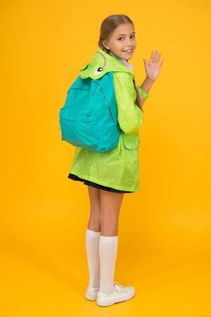 Rain is not hindrance. Schoolgirl raincoat going to school waving hand. Waterproof fabric for your comfort. Rainproof accessory. Waterproof clothes. Kid girl happy wear raincoat. Waterproof cloak