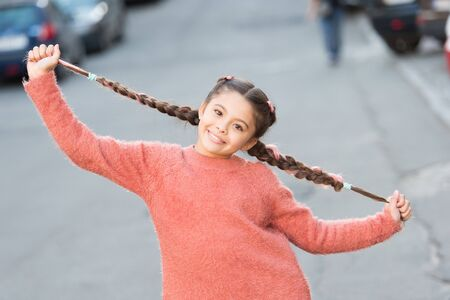 Child smile on cute face outdoors. Little happy girl braided hairstyle. Good mood concept. Beautiful kid with fresh look and skin. International childrens day. Happy childhood. Happy and positive