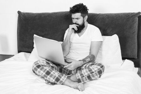 Just woke up and already at work. Man surfing internet or work online. Hipster bearded guy pajamas freelance worker. Remote work concept. Social networks internet addiction. Online shopping