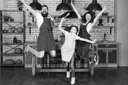 Having fun in kitchen. Family mom dad and little daughter wear aprons jump in kitchen. Family having fun cooking together. Teach kid cooking food. Weekend breakfast. Cooking with child might be fun
