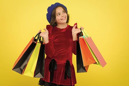 Kid girl hold bunch shopping bags or birthday gifts packages. Birthday shopping concept. Child cute small girl on shopping tour. Best price. Buy now. Visit shopping mall. All i want for my birthday