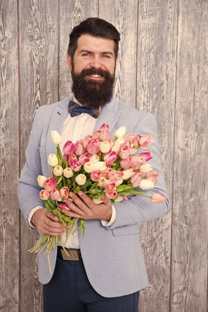 Unique flower arrangements. Spring gift. Bearded man hipster with flowers. Flower for March 8. Love date. international holiday. Womens day. Bearded man with tulip bouquet. Spring flower bouquet