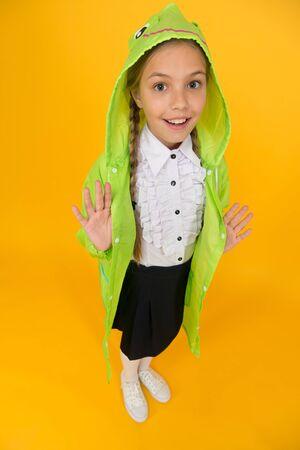 Schoolgirl hooded raincoat going to school. Waterproof fabric for your comfort. Rainproof accessory. Waterproof clothes. Kid girl happy wear raincoat. Rain is not hindrance. Waterproof cloak