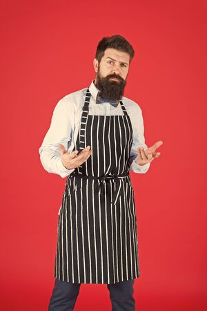 How can I help you. Man with beard cook hipster apron. Hipster chef cook red background. Bearded man chef cooking. Restaurant staff and service. Well groomed waiter at work. Hipster cafe concept