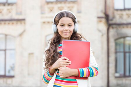 Distant education. Listening school book. Digital technologies for learning. Elearning and modern methods. Schoolgirl hold workbooks and headphones. Technologies for studying. Modern technologies