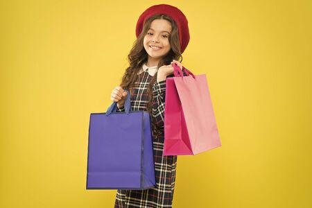 big sales. happy girl with long curly hair in beret. shopping. child with shopping bag. parisian child on yellow. little beauty shopaholic. Holiday present. little girl in hat. shopping sales