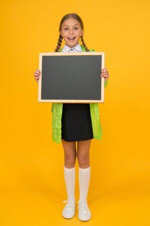 Schoolgirl wear raincoat hold blank chalkboard copy space. Waterproof fabric for comfort. Rainproof accessory. Waterproof clothes. Kid girl happy wear raincoat. Waterproof cloak. Weather forecast Imagens