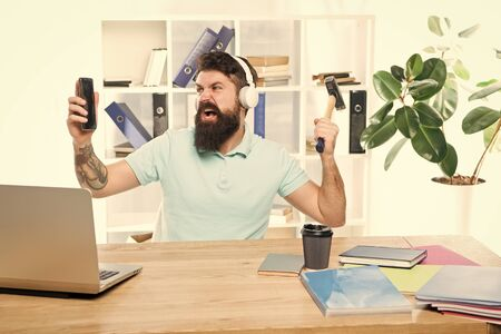 Most annoying thing about work in call center. Incoming call. Annoying client calling. Man bearded guy headphones office swing hammer on smartphone. Spoiled communication. Failed mobile negotiations