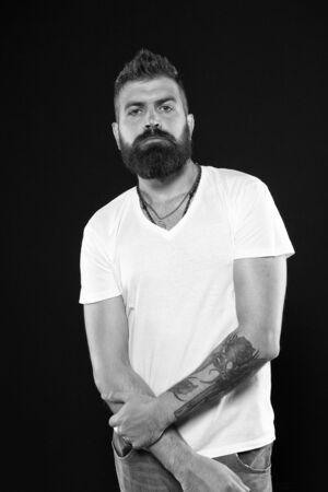 Brutal and masculine. Brutal caucasian man with long beard on black background. Brutal hipster with tattooed arms in casual style. Bearded man with brutal look