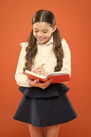 small girl in school uniform. get information form book. back to school. Small girl with workbook for writing. schoolgirl writing notes on orange background. notes in workbook. workbook information