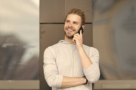 Happy to hear you. Man bearded walks with smartphone, urban background. Man pleasant smiling face speaks on smartphone. Guy pleased answer call on smartphone. Pleasant conversation with friend