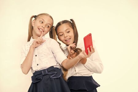 Girls school uniform take selfie smartphone. Posing to take perfect photo. Girlish leisure. Girls just want to have fun. Schoolgirls cute hairstyle use mobile phone or smartphone to share photos 版權商用圖片