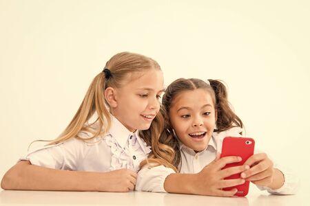 Modern life concept. Little children girls study smartphone as integral part of modern life. little girls with cell phone. Imagens