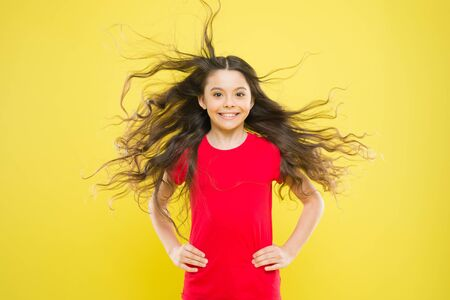 Things you doing to damage your hair. Girl adorable kid long wavy hair yellow background. Wind can also damage hair. Strong persistent winds can create tangles and snags in wavy and curly long hair