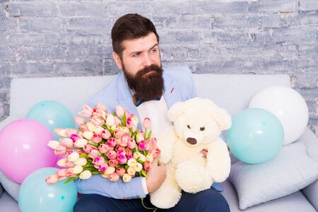 Romantic man with flowers and teddy bear sit on couch with air balloons waiting girlfriend. Romantic gift. Macho ready romantic date. Man wear tuxedo bow tie hold bouquet. She deserve all best Standard-Bild