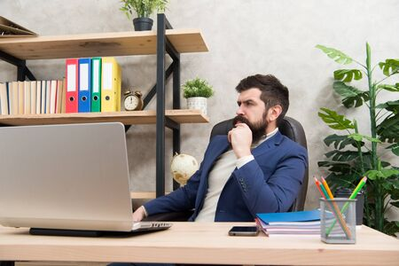 Responding on business e-mail. Brutal businessman in office. Mature man with beard work on laptop. bearded hipster use computer. Male boss working. Keeping business on top with digital technologies Foto de archivo