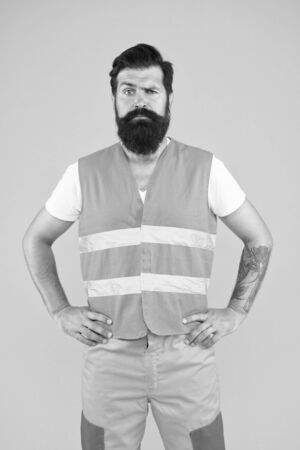 Brutal and professional. Brutal caucasian man with long beard on yellow background. Brutal hipster with tattooed arms wearing work clothes. Bearded worker with brutal look