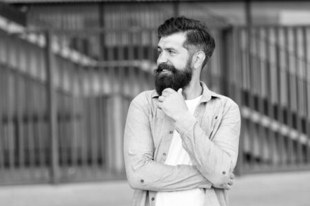 What is on his mind. Pensive hipster thinking pleasant thoughts. Man bearded hipster urban background. Regular walk in city center. Confident hipster stand in street alone. Right here and now
