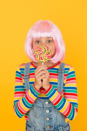 Sweet tooth. Little child hold lollipop candy yellow background. Small girl with rainbow swirl candy on stick. Adorable kid enjoy sugar candy dessert. Best candy shop.