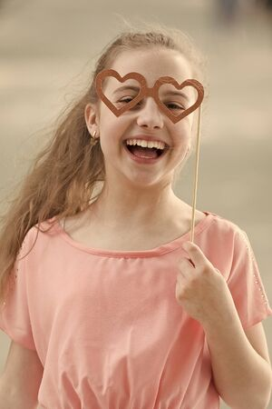Happy valentines day. Small child with happy smile and funny look through heart shaped glasses. Happy little girl smiling with photobooth props on stick. Celebrating happy international childrens day Stock fotó