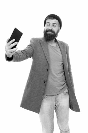 No selfie stick required. Happy hipster taking selfie with smartphone in hand. Bearded man smiling to selfie camera. Selfie with confidence