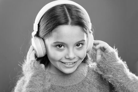 Girl cute little child wear headphones listen music. Kid listen music orange background. Recommended music based on initial interest. Tell me what you listen to, and I will tell you who you are