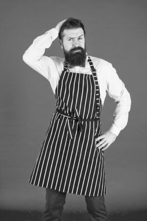 I need a new hairstyle. Mens barber touching head hair. Bearded man wearing barber apron. Stylish hipster in elegant work apron. Hair stylist in barber shop. Barbershop or hairdressing salon Stock Photo