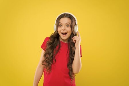 Technology is wonderful when it works. Happy little girl listening to music in earphones on yellow background. Small child enjoying stereo sound technology. New technology. Technology concept