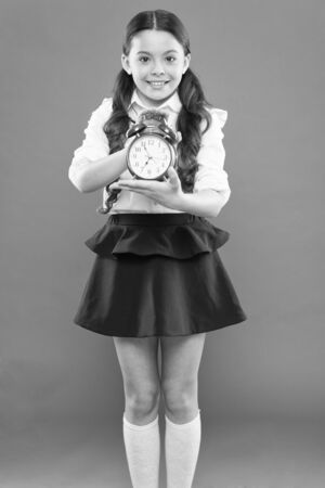 Time to study. Classes begin. Developing discipline. Time for break and relax. Vacation time. Elementary school day bell schedule. Schooltime concept. Schoolgirl child formal uniform hold alarm clock Banque d'images