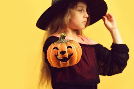 Dziecko w czarnym kapeluszu i sukience czarownicy. Dziewczyna z dynią Zdjęcie Seryjne