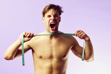 Screaming man with blue measuring tape on light purple background Banco de Imagens
