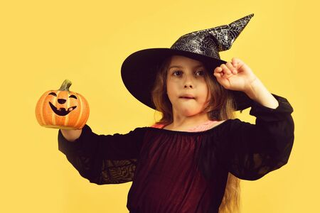 Girl with carved orange pumpkin isolated on warm yellow background Banque d'images