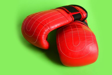 Sport boxing gloves in red colour for martial arts isolated on green background. Concept of sports and professional fight 写真素材