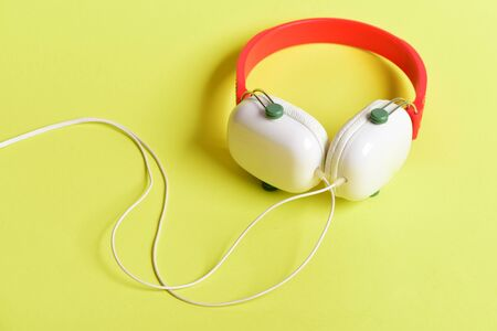 Headset for music made of plastic. Modern and stylish earphones on yellow background. Music accessories and technology concept. Headphones in white and red color with long wire Standard-Bild - 133249081