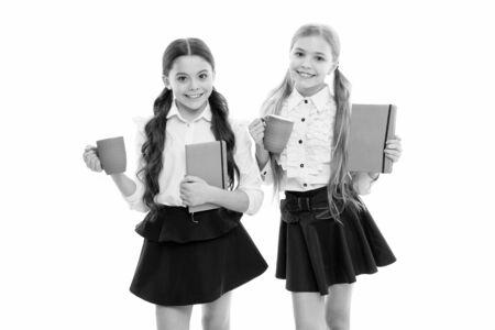 Taking a few minutes break from their books. Little schoolgirls having tea with milk for break. Small school children holding cups at meal break. Cute girls enjoying school break