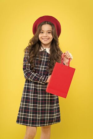 Purchase the trend. Little girl smiling with personal purchase on yellow background. Happy small child holding her purchase in red paperbag. Buying fashion purchase for kids