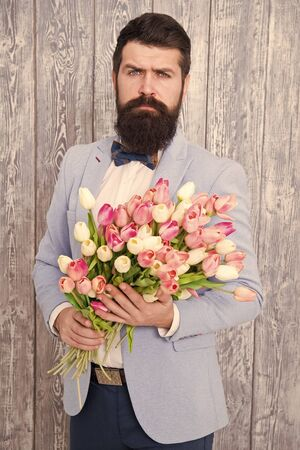 To say I love you. Womens day. Flower for March 8. Spring gift. Bearded man hipster with flowers. Bearded man with tulip bouquet. Love date. international holiday. Love spring. Show your love